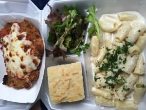 Rigatoni Alfredo with chicken parmesan, accompanied by a side of green salad and focaccia bread.