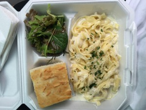 Fettuccini Alfredo with chicken, accompanied by a side of green salad and focaccia bread.