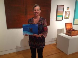 Scholarship Chair Debbie von Tempsky poses at Art Maui 2016 with books featuring scholarship winners' art.