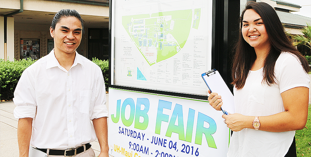Two students standing next to the UHMC Job Fair sign