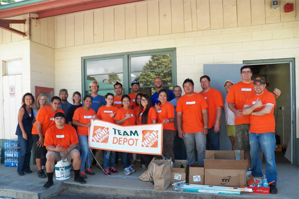 Group of volunteers holding a Team Depot Sign outside of the VRC building