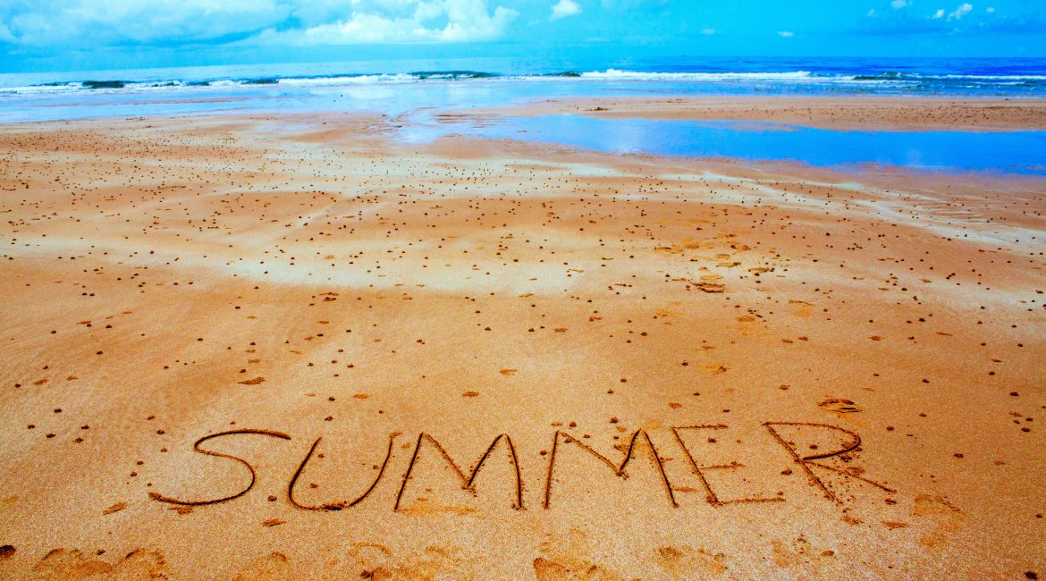 """The word """"summer"""" written in the sand."""