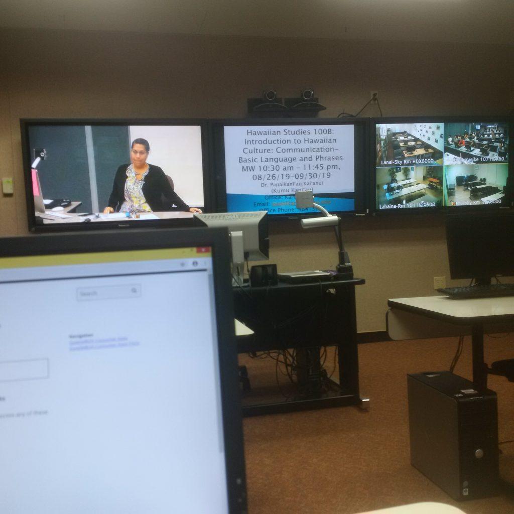 photo of three monitors at front of room.